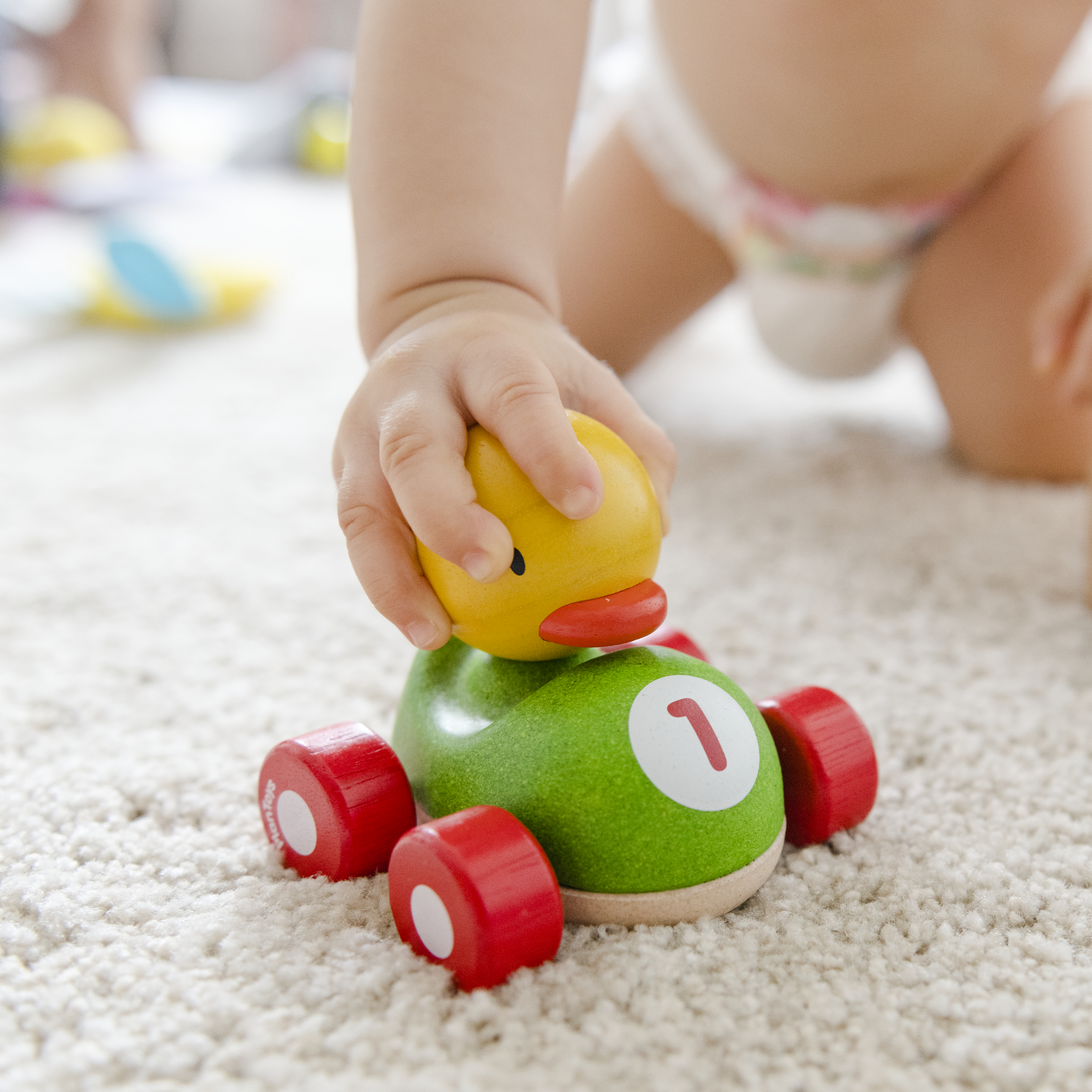 Baby playing with a wooden car